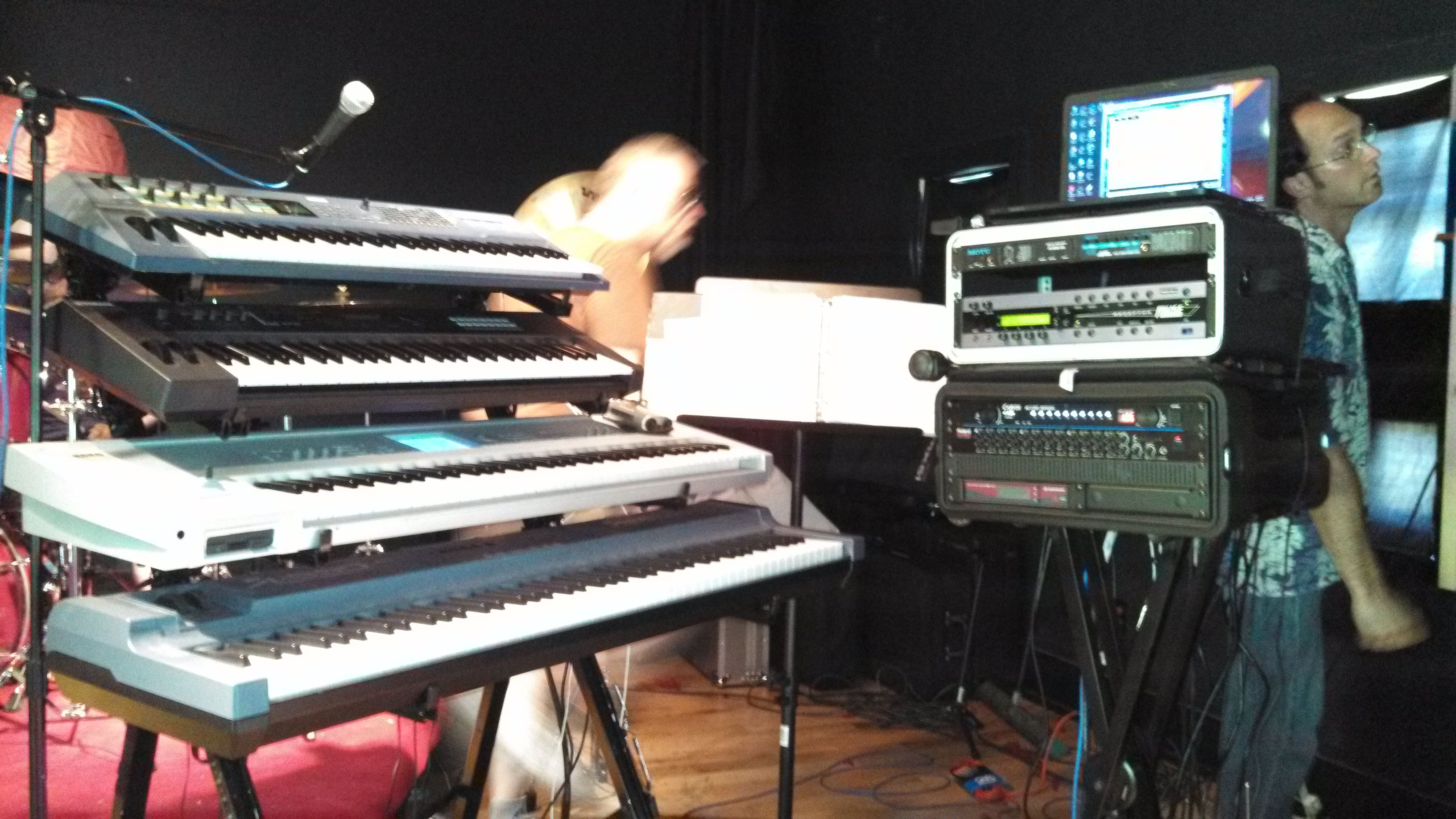 Bill runs behind Andrew's keyboard rig, while engineer Paul Ilsley tries to figure out the backstage monitor setup.