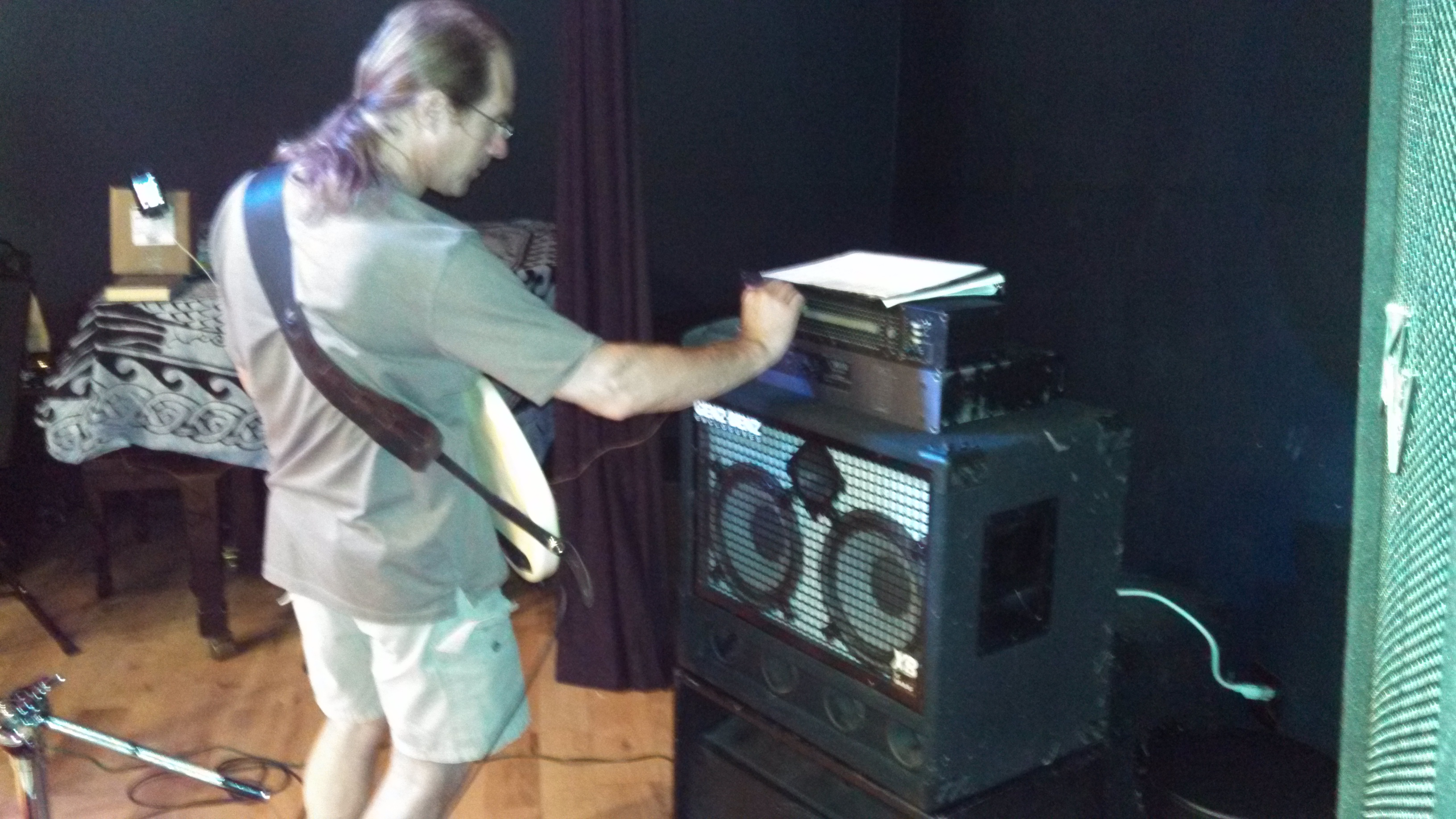 Dave adjusts his bass amp to get just the right volume and tone.